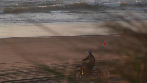 A dirtbiker makes tracks on a sandy beach during the... Stock Video Footage