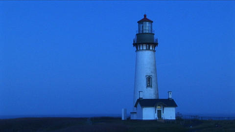 A white flashing beacon breaks up the blue tones of this footage of a lighthouse Footage