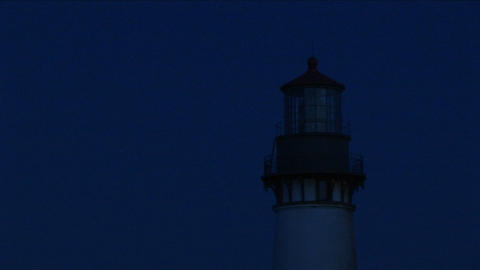 A close-up of the beacon at top of lighthouse tower at night Footage