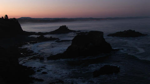 A broad band of pink and orange sky brightens this footage of a gray, rocky coastline Footage