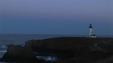 Long-shot of a white lighthouse with its beacon flashing... Stock Video Footage