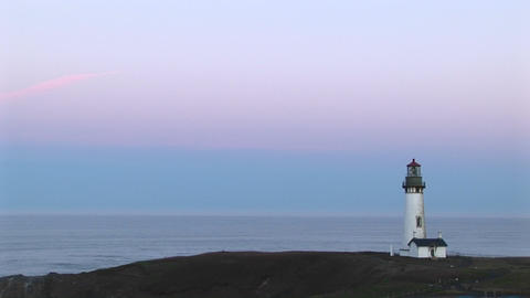 A montage of lighthouse longshots with a pastel sky above a quiet ocean Footage