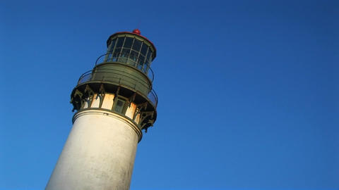 A telephoto view of the top of a lighthouse and its circular decks with 360-degree views of the hor Footage