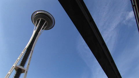 A worms-eye angled-view of Seattle's Space Needle and the underside of the monorail that runs nearby Footage