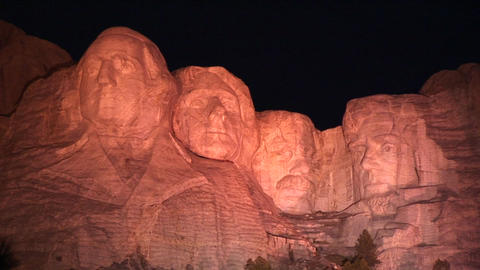 Mt. Rushmore is bathed in warm light at night Stock Video Footage