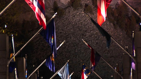 The camera pans up the Avenue of Flags to Mt. Rushmore at night in lights Footage