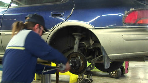 A mechanic pulls repeatedly on a wheel's axle Stock Video Footage