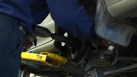 A mechanic works on a wheel repair with a variety of tools Footage