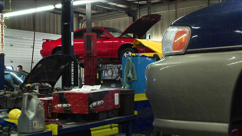 Medium-shot of cars in for repairs and a customer in the background talk to a mechanic Live Action