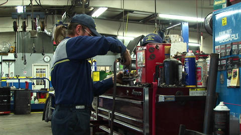 Medium-shot of an auto mechanic working in a garage Stock Video Footage
