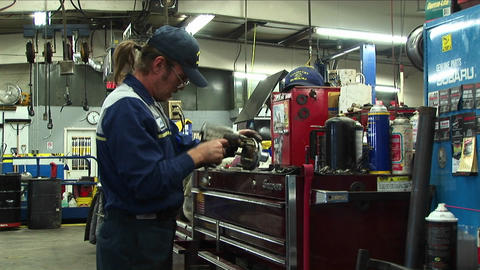 Medium-shot Of An Auto Mechanic Working In A Garage stock footage