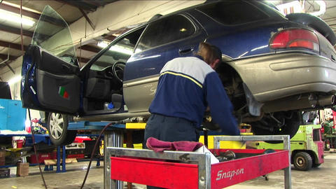 A mechanic uses a wrench to work on the wheel-mount of an... Stock Video Footage