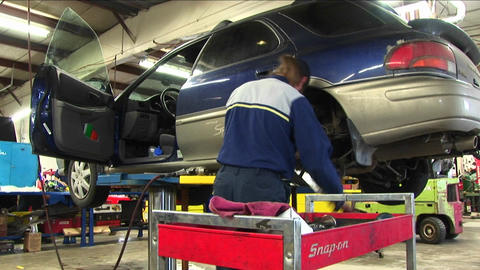 A mechanic uses a wrench to work on the wheel-mount of an auto on a hydraulic lift Footage