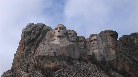 Clouds drift slowly past the tops of the four presidents in this long-shot of Mt. Rushmore Footage