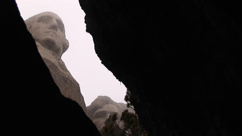 The camera pans through a small opening at the base of Mt. Rushmore for a worms-eye view of George W Footage