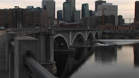 Pan-up from bridge on Mississippi River to skyline of Minneapolis, Minnesota Footage