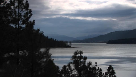 A scenic view of an ocean inlet and shoreline with trees and hills in grays and blues Footage