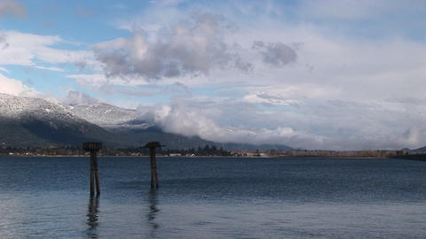 The camera looks over a Lake Pend Oreille Idaho to the mountains dusted with snow in the distance Footage