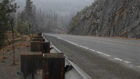 A look at a quiet mountain road during a winter snowstorm Stock Video Footage