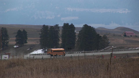 A yellow school bus travels along a rural road to pick up... Stock Video Footage