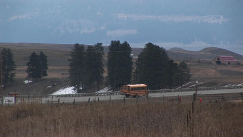 A yellow school bus travels along a rural road to pick up its passengers Footage