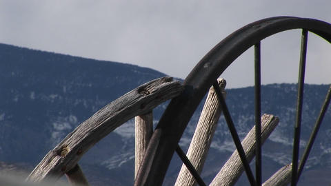 Camera looks at mountains through the broken spokes of abandoned wagon wheels Footage