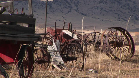Broken and rusty, vintage wagon-wheel rims and other old equipment are abandoned in the dry prairie Footage