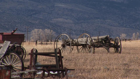 A Scenic Look At Old Wagons And Other Vintage Equipment Abandoned On The Prairie With The Mountains stock footage