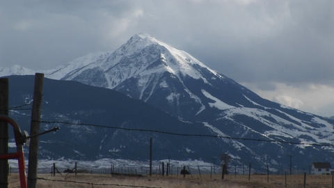 A snow-capped mountain watches over a ranch with barbed-wire fences Footage