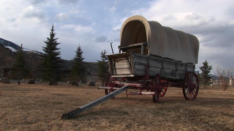 A covered wagon looks right at home against the backdrop of evergreens and prairie Footage
