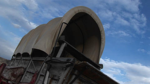 Worms-eye view of a covered wagon against a blue sky Footage