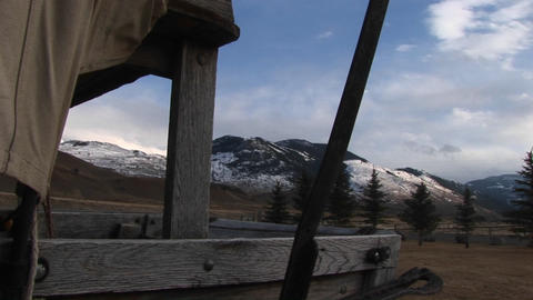 The camera looks through an opening in a covered wagon for a view of the mountains beyond Footage