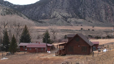 A rural homestead sits at the foot of a mountain range Stock Video Footage