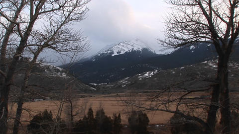 Snow-clouds begin to form above the snow-capped mountain in the distance Footage