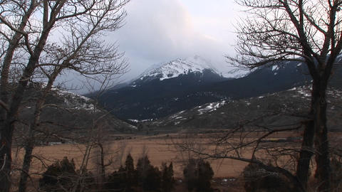 Snow-clouds begin to form above the snow-capped mountain... Stock Video Footage