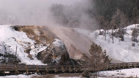 Mist rises from Yellowstone National Park's hot springs' terraces in winter Footage