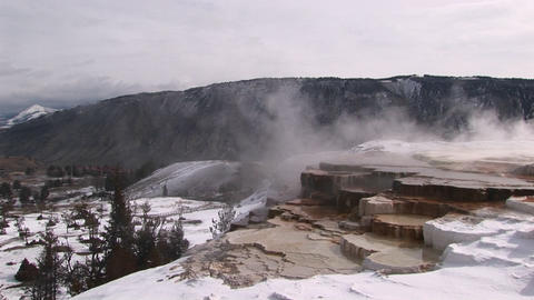 A look at hot springs' limestone terraces in winter with scenic mountains in the background Footage