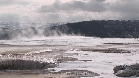 The camera captures the wind blowing the steam rising from the hot springs' terraces Footage