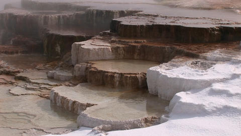 A colorful close-up look at a hot springs limestone terrace with steam snow and thermal pool Footage