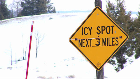 A winter warning sign for drivers and a bright red snow pole are the main focal points of this clip Footage