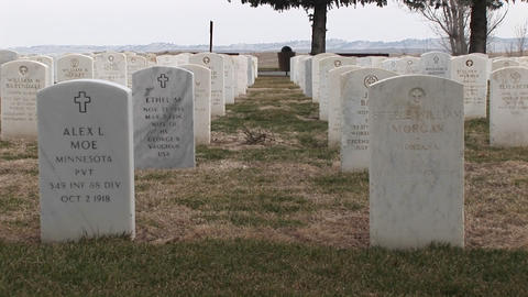 The camera pans right across rows of white headstones in an old military cemetery Footage