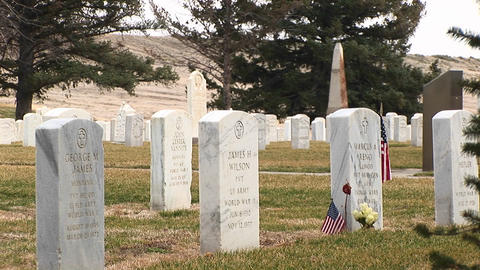 An American flag and flowers decorate one of so many headstones at Arlington National Cemetery Footage