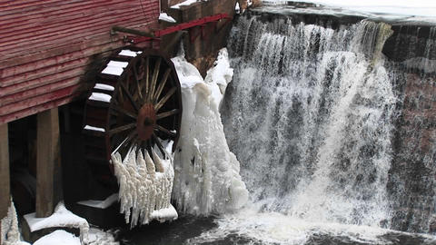 A close-up of water flowing past a gristmill whose waterwheel is immobilized by freezing temperature Footage