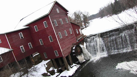 An angled view of a mill with waterwheel and dam in winter Footage