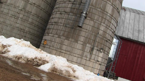 Camera pans up the sides of two grain silos Stock Video Footage