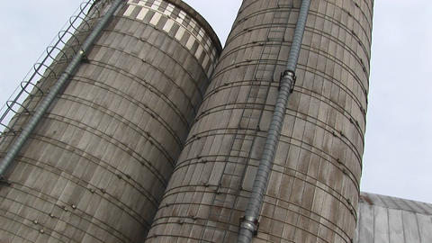 Camera pans up the sides of two grain silos Footage