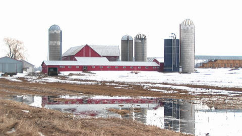 Long-shot of farm barns and silos on a winter's day Footage