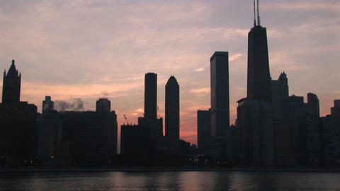 A golden-hour Chicago skyline with silhouetted buildings against a pink and orange sky Footage