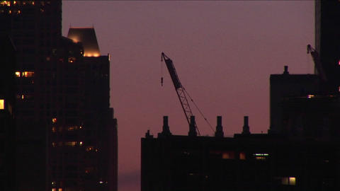 A building crane rests on a rooftop in a golden-hour skyline shot Footage