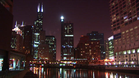 A commuter train moves slowly across the brilliant Chicago skyline at night Footage